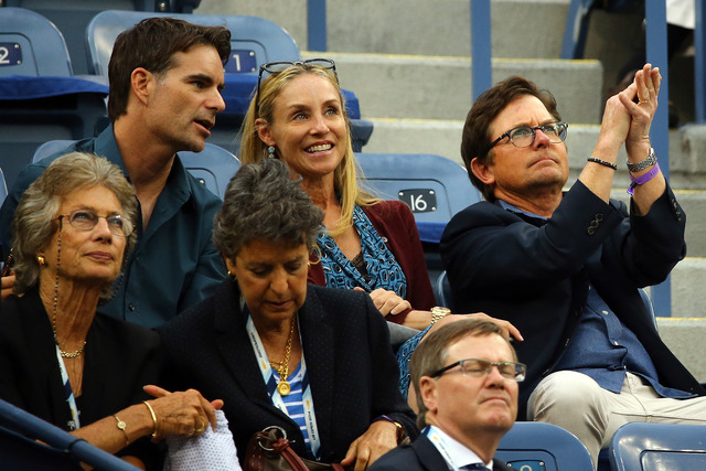 NASCAR driver Jeff Gordon, Tracy Pollan and Michael J. Fox watch Kei Nishikori of Japan plays against Marin Cilic of Croatia on Day fifteen of the 2014 US Open.