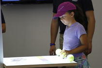 A child interacts with a display at the US Open American Express Fan Experience.