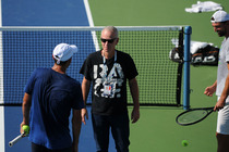 John McEnroe spotted kidding around with players on the practice courts at the 2014 US Open.