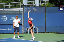 Cara Black practices her serve on Court 13 as her coach looks on.