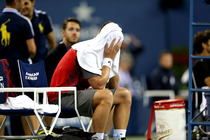 Sam Groth puts a towel over his head during his match against Roger Federer.