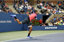 Nick Kyrgios lands after hitting a serve in Arthur Ashe Stadium.