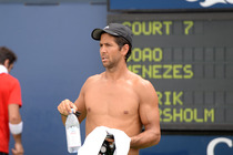 Fernando Verdasco grabs a drink during a practice session on Day 7 of the Open.